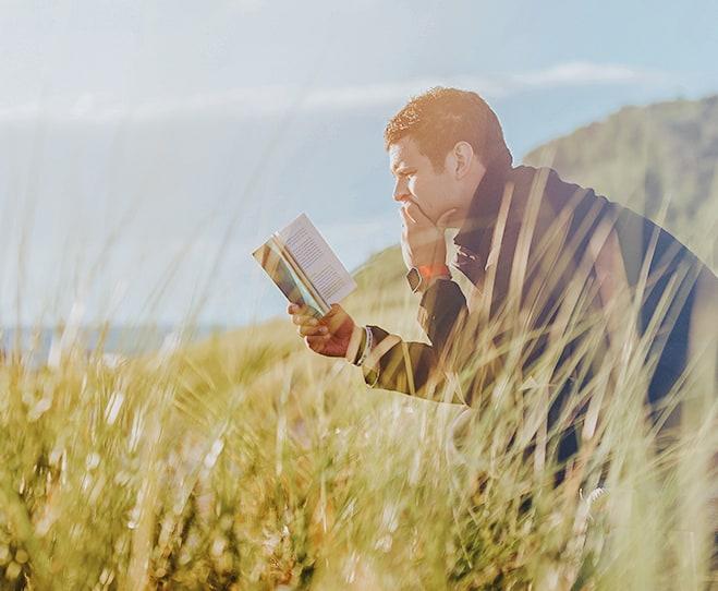 Čovek čita knjigu u prirodi