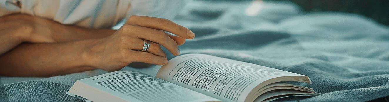 Devojka čita knjigu na krevetu.
