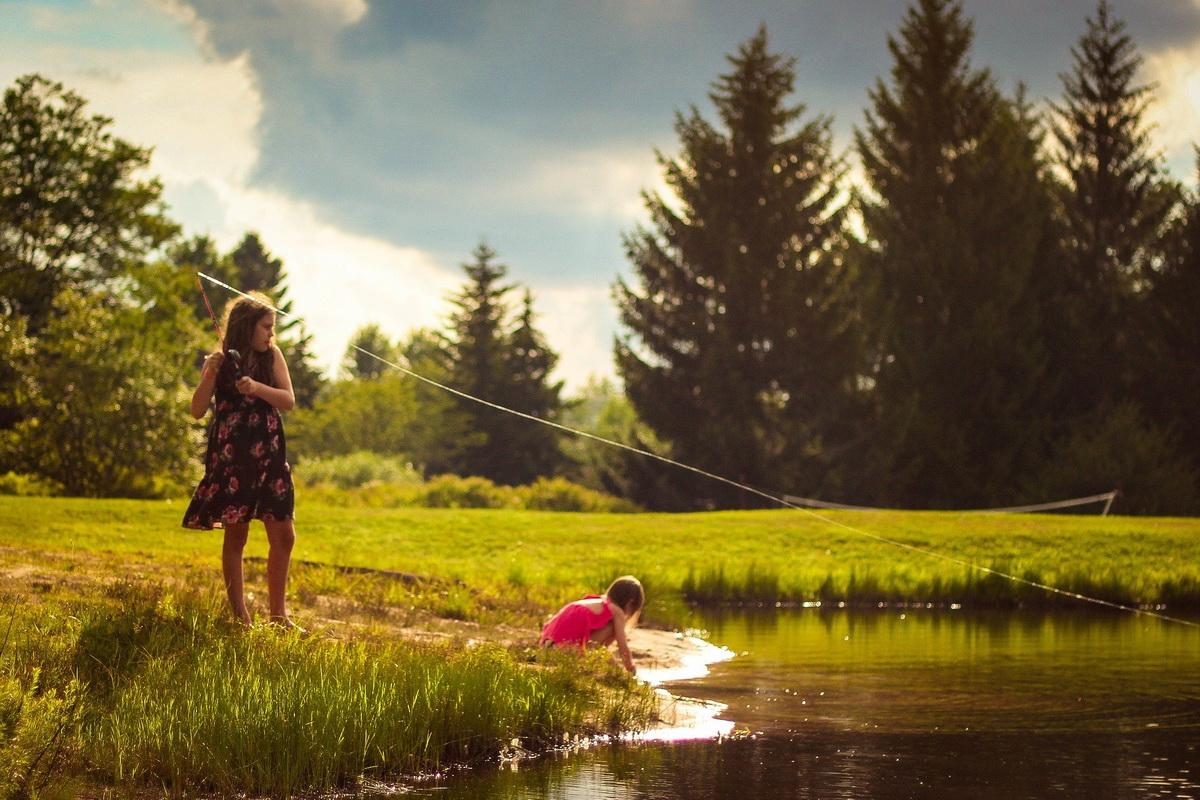 Devojčice pecaju u prirodi po sunčanom danu.
