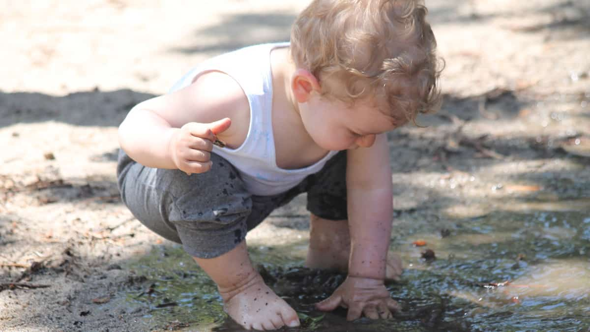Bosonogi dečak se igra u blatu