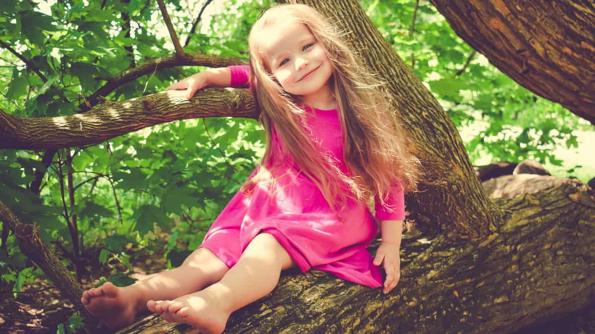 Nasmejana devojčica sedi na grani drveta