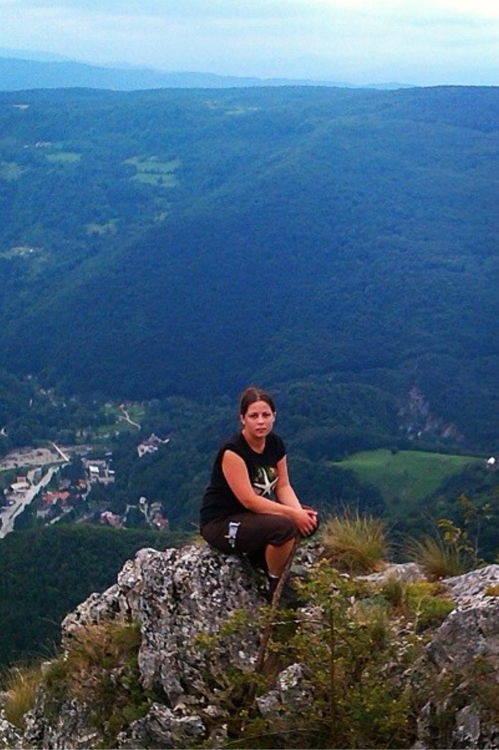 Devojka sedi na kamenu na vrhu planine ili brda.