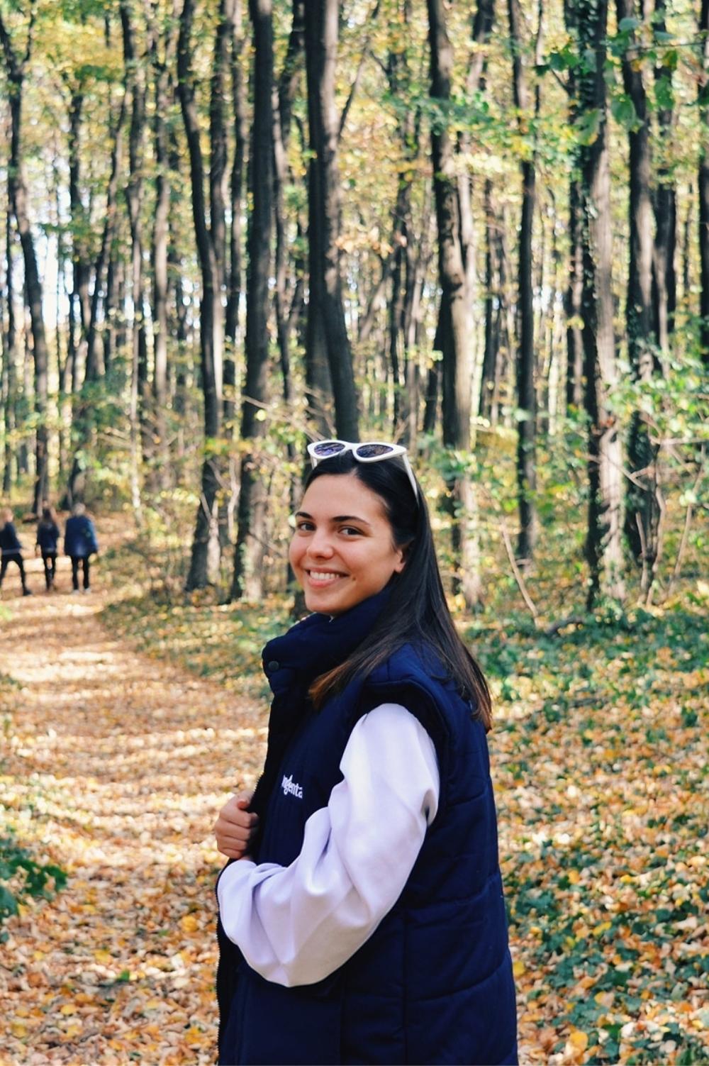 Devojka u prijatnoj šetnji kroz park šumu.