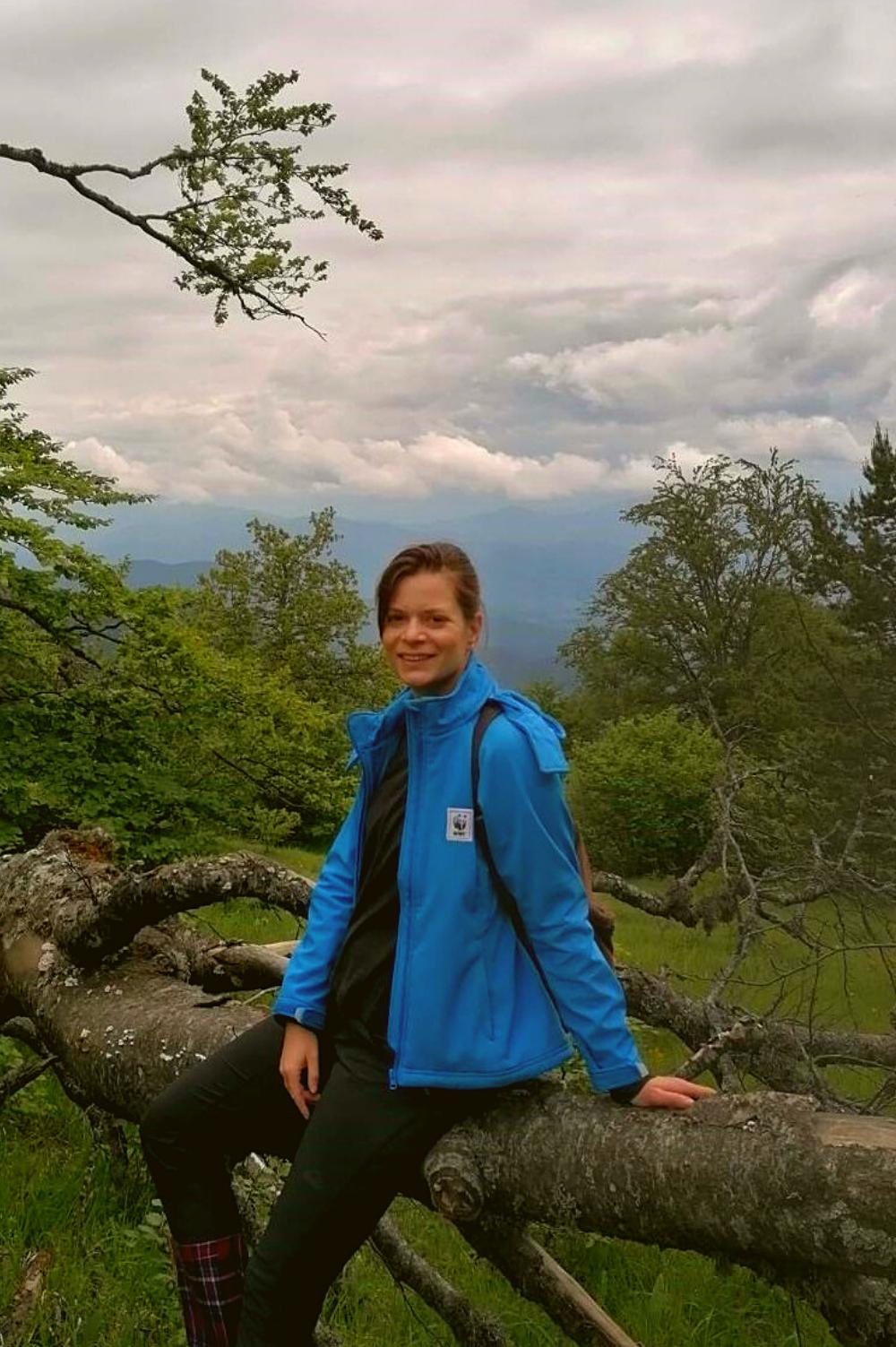 Devojka sedi na oborenom drvetu na brdu.