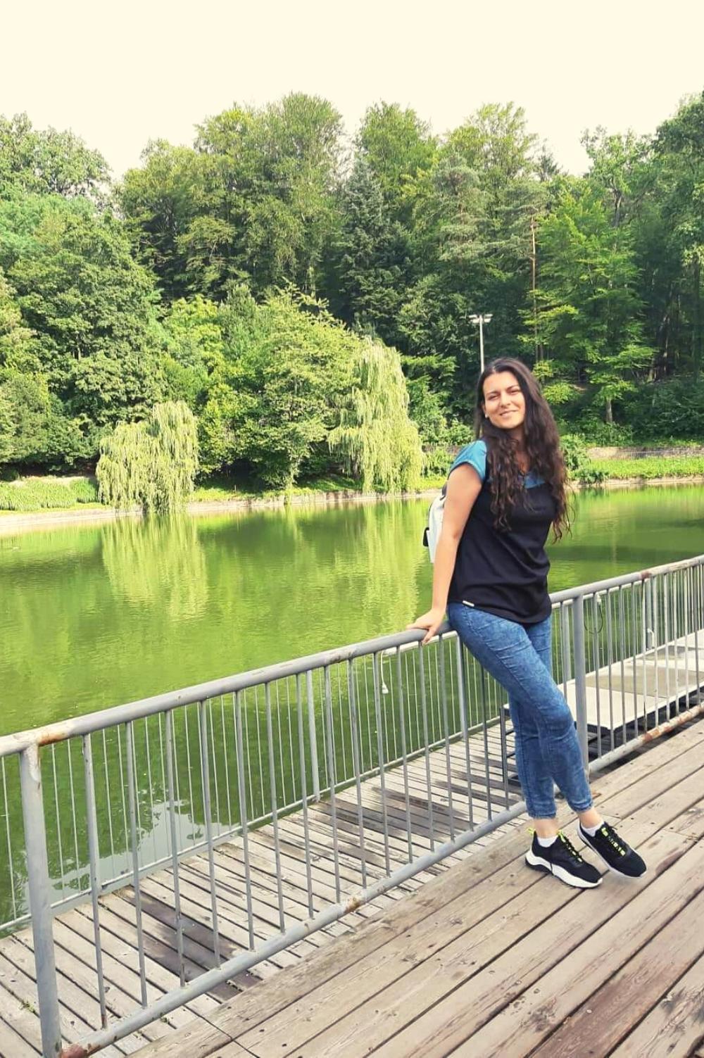 Devojka sedi na ogradi na šetalištu pored reke..