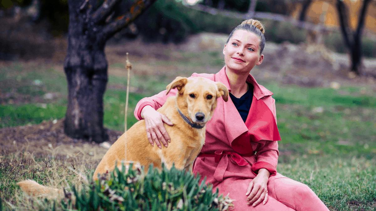 Devojka grli svog psa i zajedno uživaju u prirodi